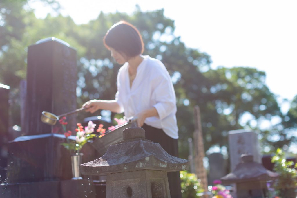 お墓に水を撒く女性