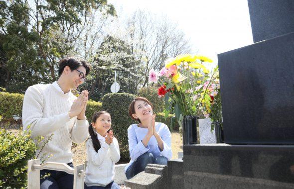 家族3人でお墓の前で手を合わせる