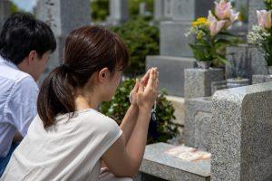 お墓の前で男性と女性が手を合わせる