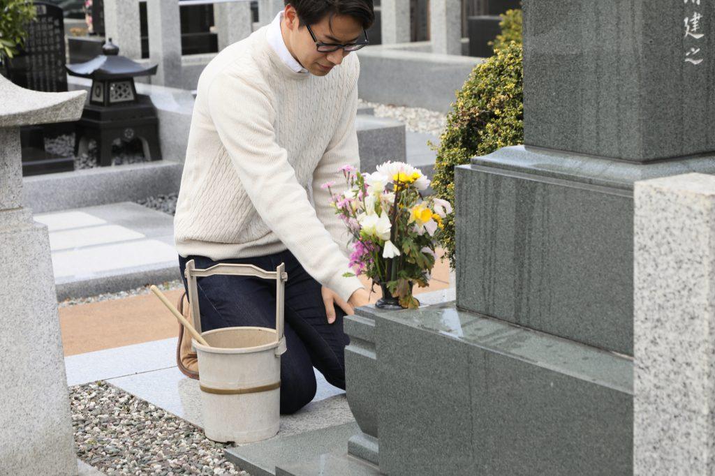 一人でお墓のお手入れをする男性