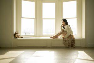 窓辺で猫を見ながら微笑む女性
