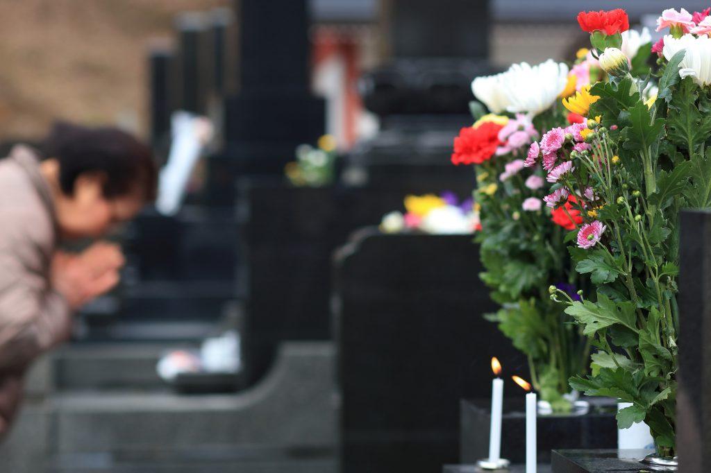 お墓参りしている女性とお花
