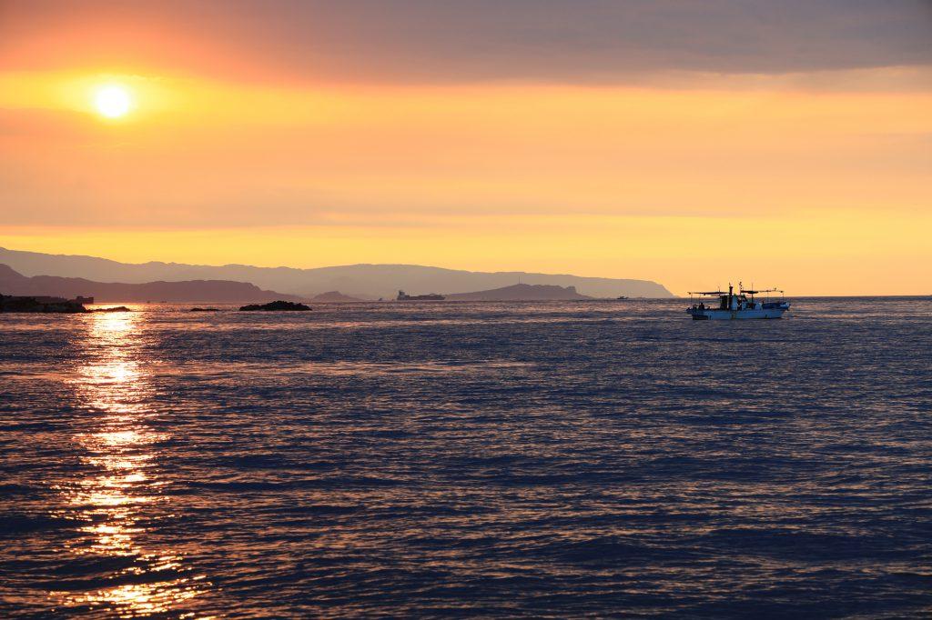 夕焼けの海に浮かぶ船