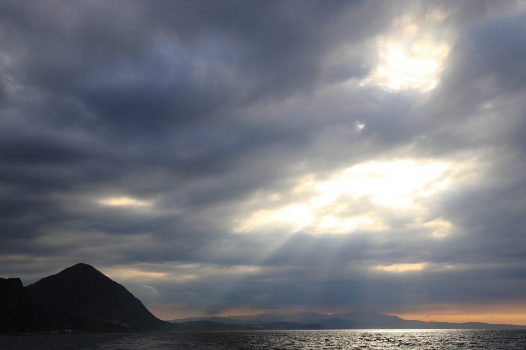 雲の隙間から光が指す海
