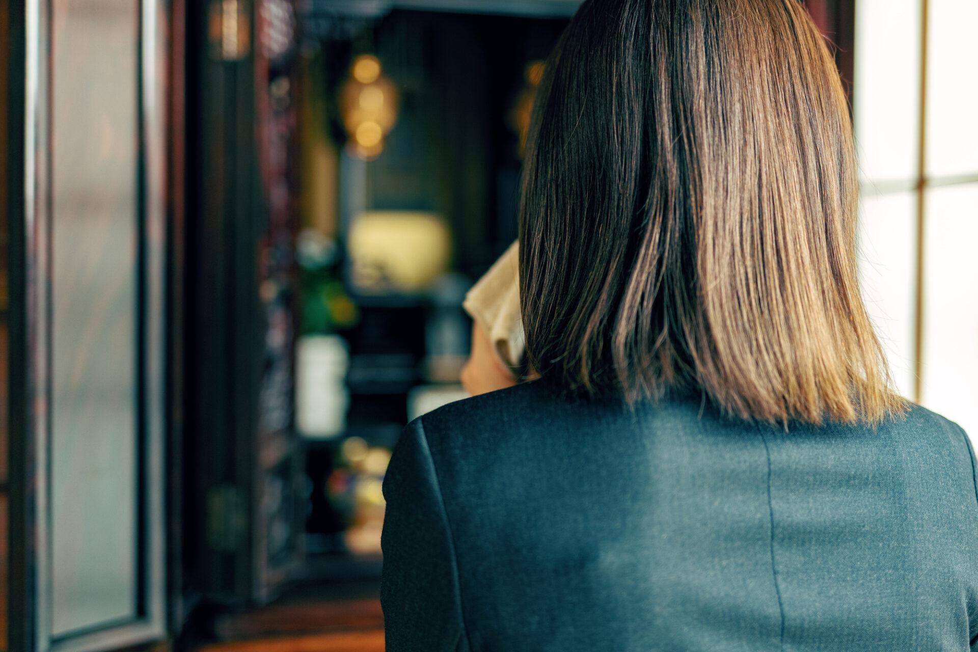 スーツを着た女性が仏壇の前で手を合わせる
