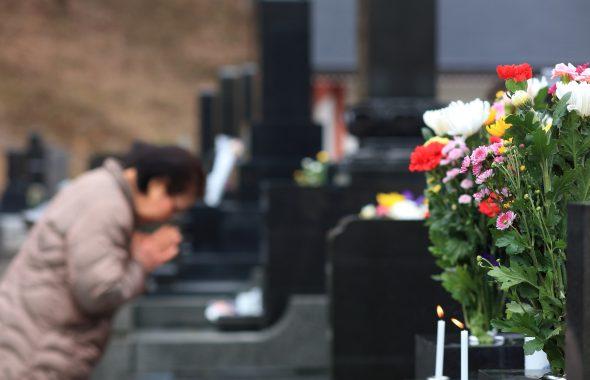 お墓に祈りをささげる女性