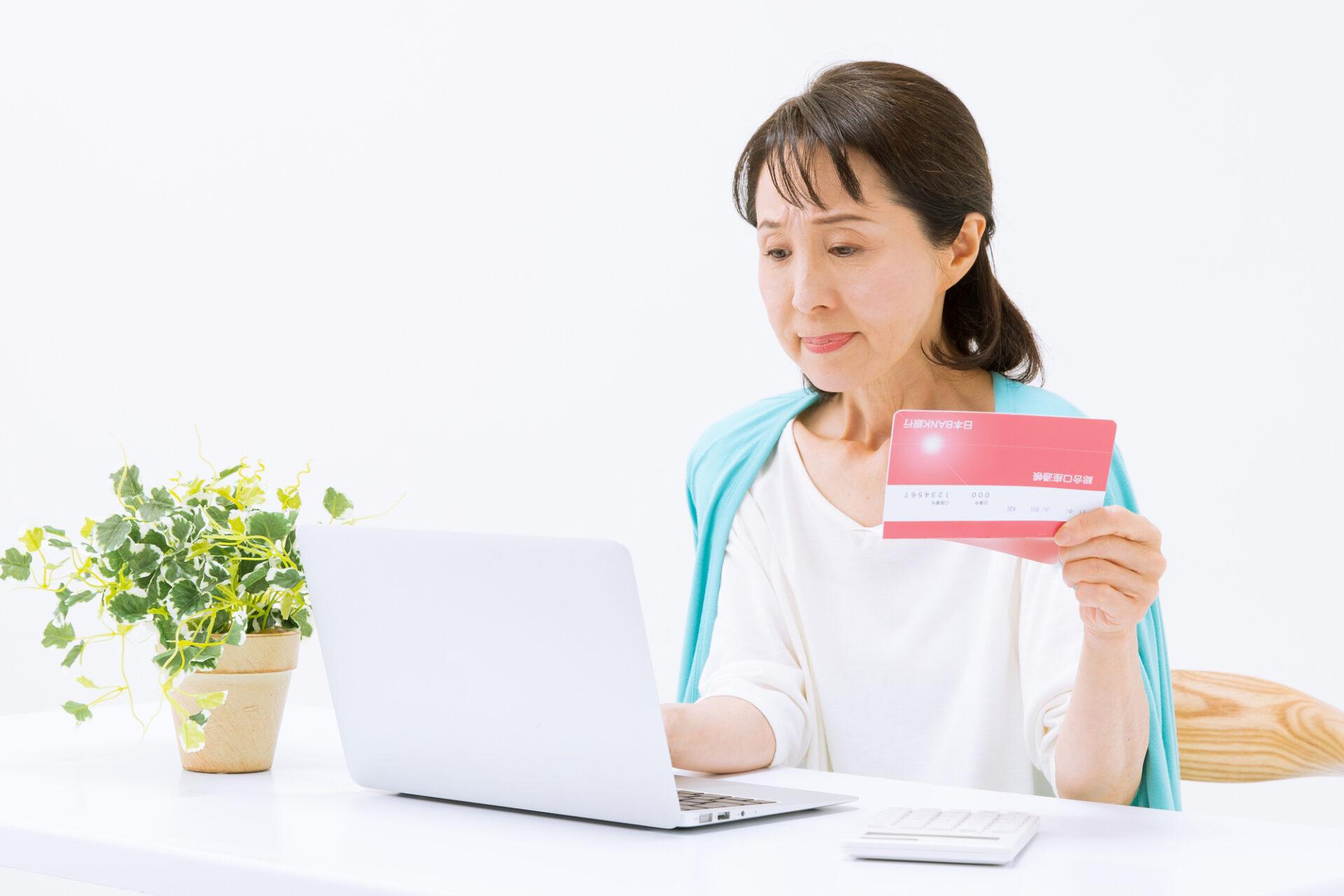 通帳とパソコンを見る女性