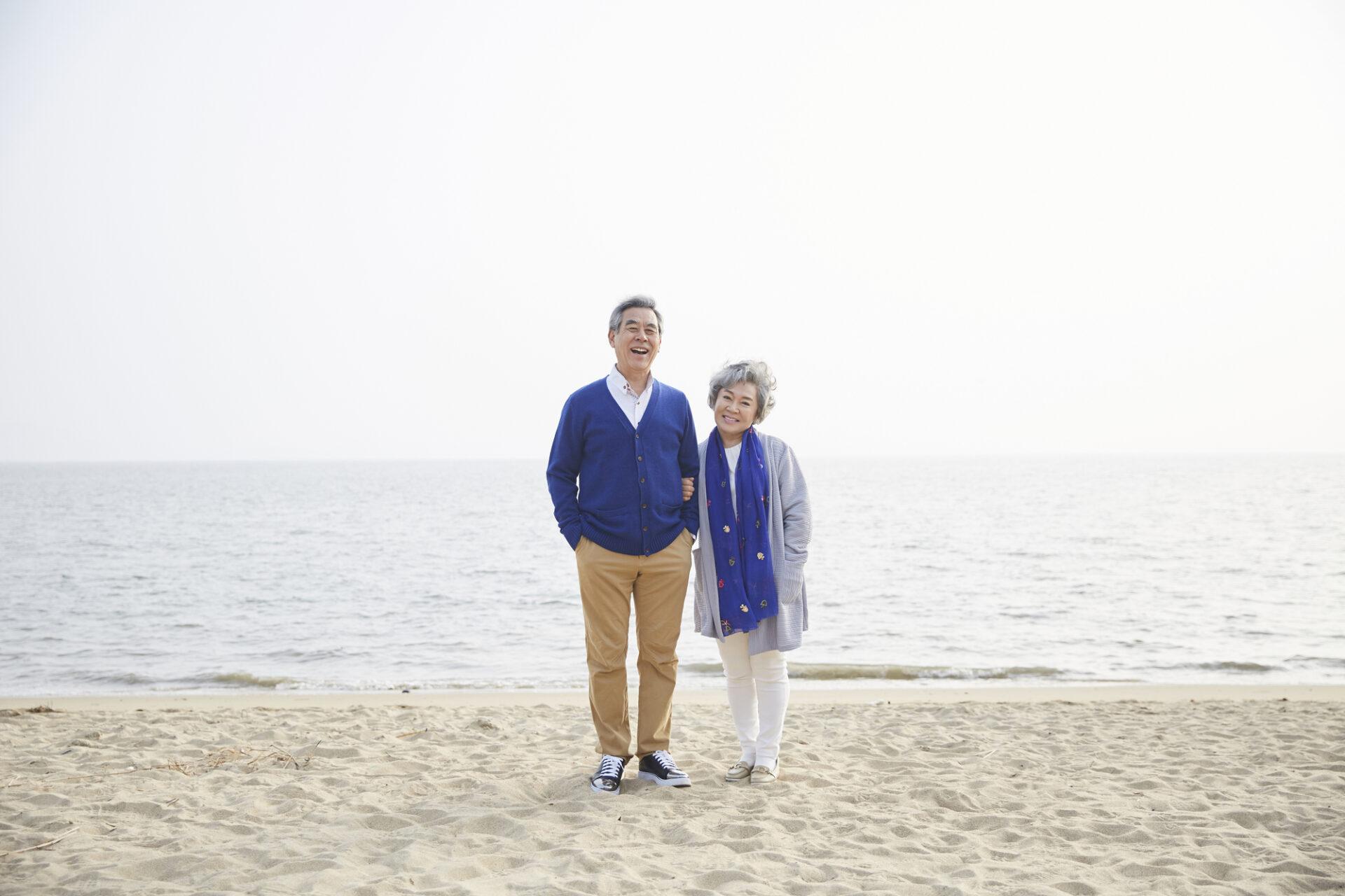 年配の男女が砂浜で写真を撮る